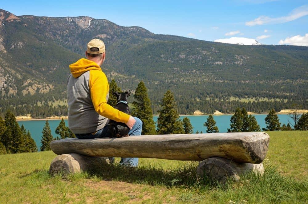 Mann mit Zwergpinscher an einem Bergsee